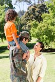 stock photo of reunited  - Happy soldier reunited with family on a sunny day - JPG