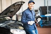 picture of steers  - Portrait of an auto mechanic holding a jug of motor oil - JPG
