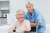 stock photo of wheelchair  - Portrait of confident nurse leaning on senior patients wheelchair at clinic - JPG