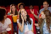 picture of annoyance  - Annoying woman on the phone during movie at the cinema - JPG