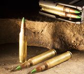 picture of cartridge  - Cartridges with green tips and a loaded magazine on rocks - JPG