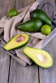 pic of avocado  - Avocado with limes on tray on wooden background - JPG