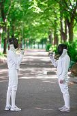 stock photo of rapier  - Two rapier fencers women staying in park alley getting ready for competition - JPG