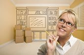 stock photo of daydreaming  - Daydreaming Woman Holding Pencil In Empty Rom with Built In Shelf Design Drawing on Wall - JPG