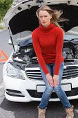 foto of annoyance  - Annoyed young woman beside her broken down car in the street - JPG