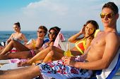 foto of sunbathers  - Group of multi ethnic friends sunbathing on a deck chairs on a beach  - JPG