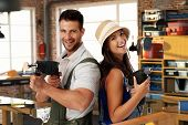 foto of hand drill  - Happy young caucasian casual couple having fun at home workshop - JPG