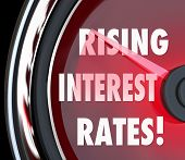 Постер, плакат: Rising Interest Rates words on a speedometer or gauge to illustrate higher costs for borrowing money