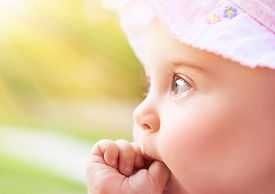 picture of finger-licking  - Closeup portrait of a sweet little baby girl in bright light of sunny day - JPG