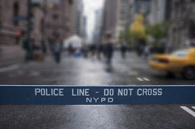 stock photo of police  - Police Line Do Not Cross. A Police line do not cross police department crime scene sign on the sidewalk in New York City.