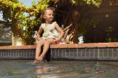 pic of dipping  - Outdoor shot of a little girl dipping her feet in the pool looking away - JPG