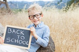 stock photo of chalkboard  - smart excited little boy in glasses holding chalkboard ready for school back to school concept - JPG