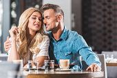 Affectionate Couple Cuddling At Table In Cafe During Date poster
