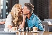 Affectionate Couple Kissing At Table In Cafe poster
