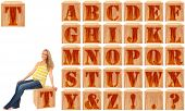 Wood engraved and stained alphabet blocks.  Featuring pregnant woman on Letter T.