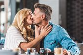 Affectionate Heterosexual Couple Kissing At Table In Cafe poster