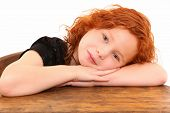 Close up beautiful curly red hair girl sitting in desk with head down over white background.