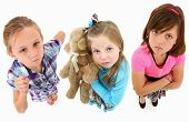 Adorable group of angry 7 year old girls over white background looking up towards camera.  Top view