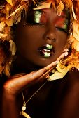 Attractive black african american woman with beautiful skin, artistic makeup, in a relaxed meditation pose.