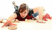 Hungry teen girl diving through baking mess to get the last sugar cookie.