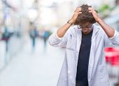 Afro american doctor scientist man over isolated background suffering from headache desperate and st poster