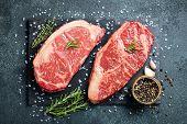 Fresh Raw Prime Black Angus Beef Steaks On Stone Board: Striploin, Rib Eye. Top View. On A Dark Back poster