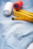 Closeup of needle with thread and ruler (sartorial meter) on jeans material.