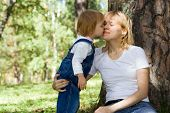 baby kiss mammy on nature