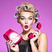 young woman with wonder face holds retro phone. Girl with blue curlers talking by red telephone. You poster