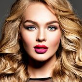 Blond woman with long curly beautiful hair. Makeup. Fashion make-up. Fashionable girl dressed in bla poster