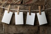 four photo paper attach to rope with clothes pins on brick background