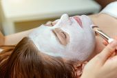 Close-up Of Young Beauty Brunette Woman Getting Face Treatment With White Nourishing Creme In Spa Sa poster