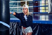 Concentrated Blonde Woman Doing A Fitness Boxing Workout With A Punching Bag. The Girl In The Boxing poster