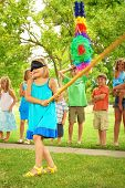 picture of pinata  - Young girl at an outdoor party hitting a pinata - JPG