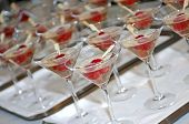 Lines of glasses filled with champagne and two raspberries on a stick, photographed with a shallow d