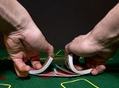 Two hands, shuffling a deck of cards, seen from the dealers point of view.