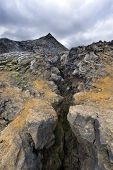 A glance in the volcanic Fissure of the 1984 eruption of the Krafla Volcanic system in Iceland. The solidified magma and lava is still hot, and provide a spectacular barren  view