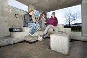 Three adolescent youths lighting cigarettes in a shelter in a suburban area