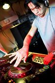 Disc jockey at work behind a turn table in a discotheque