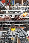 Long products in a hardware store, including materials for plumbing, flag poles, and different kinds of profiles with a shallow Depth of field