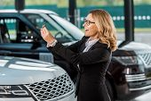 Happy Businesswoman In Formal Wear Holding Car Key From New Car In Dealership Salon poster