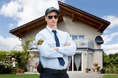 Male Security Guard Wearing Sunglasses Standing In Front Of House poster