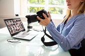 Female Editor Holding Dslr Camera With Laptop On Desk poster