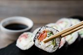 Eating Sushi. Food Photo Art, Japanese Restaurant, Dinner. Pair Of Chopsticks Taking Sushi Roll From poster