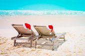Christmas On Beach -chair Lounges With Santa Hats At Sea poster