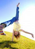 Young girl doing cartwheel across green grass