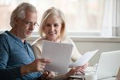 Happy Older Aged Couple Holding Reading Good News In Document poster