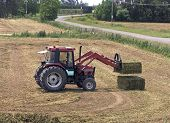 picture of hay bale  - A tractor stacking large bales of pea vine hay - JPG
