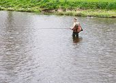 A fly-fisherman on the River Tweed, at Peebles in Scotland