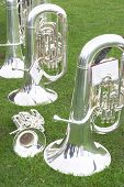 Tubas and a cornet or trumpet on the grass as a brass band takes a break during a village fair.
